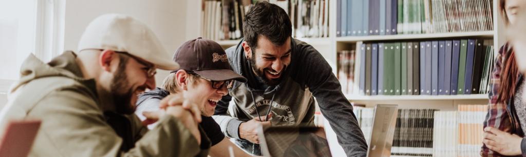 Men smiling behind a laptop